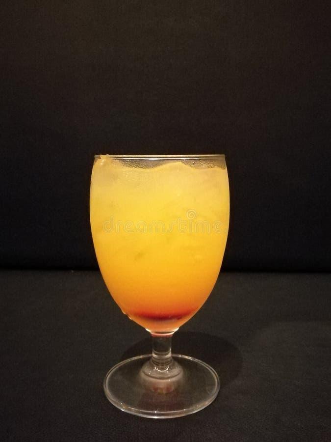 Lato napój, świeży sok pomarańczowy, mocktail z sodą i kostka lodu, miękki napój z lodem na szkle z plamą odizolowywamy czarnego  zdjęcie royalty free