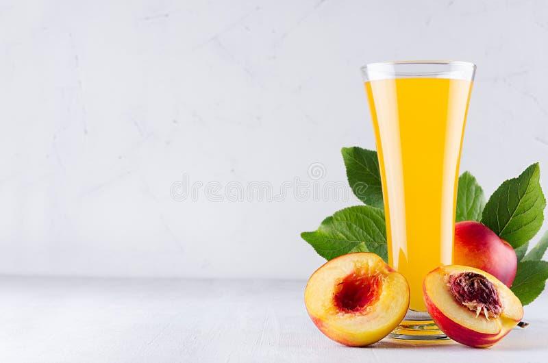 Lato napój brzoskwinia sok, czerwone dojrzałe nektaryny z liśćmi i mięsisty plasterek na miękkiego światła białym drewnianym tle  obraz royalty free
