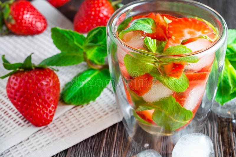 Lato napój truskawki i mennica z kostka lodu na ciemnym drewnianym stole zdjęcia stock