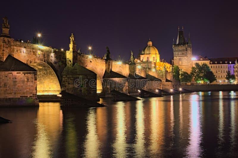 Lato nocy widok dziejowa część Praga Vltava rzeka, Mala Strana mosta wierza i Charles most z iluminacją, obraz royalty free
