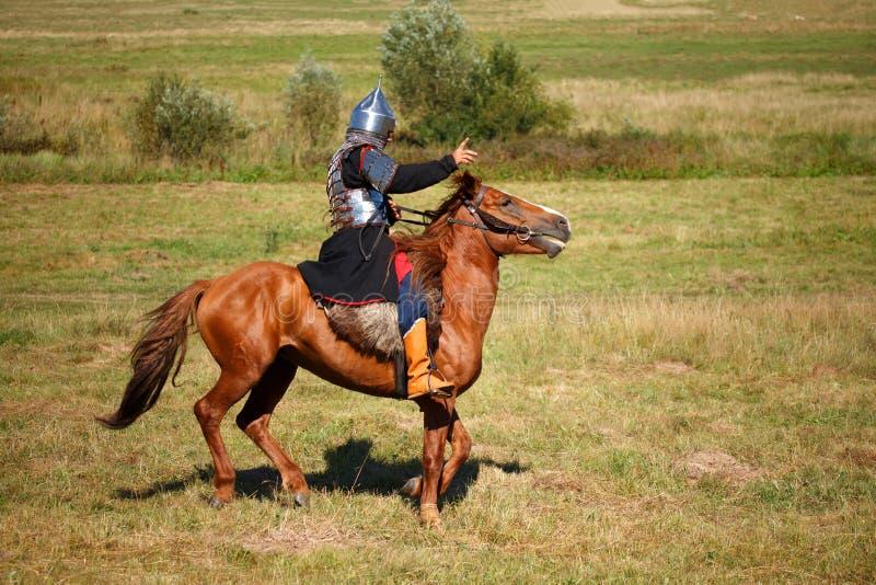Lato odbudowa Średniowieczny opancerzony rycerz na koniu Equestrian żołnierz w dziejowym kostiumu Reenactor obraz royalty free