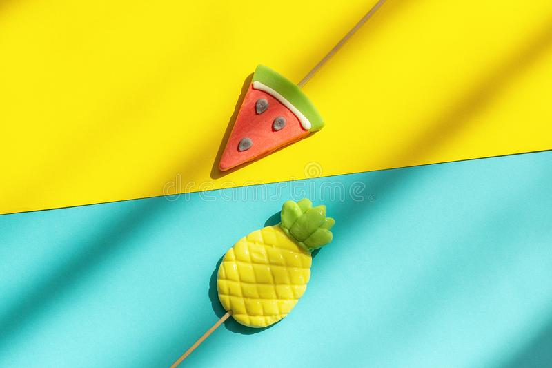 Lato owoc ananas i arbuzów lizaki na kiju na błękitnym żółtym tle z ciężkim światłem i cieniem Poj?cie obrazy royalty free