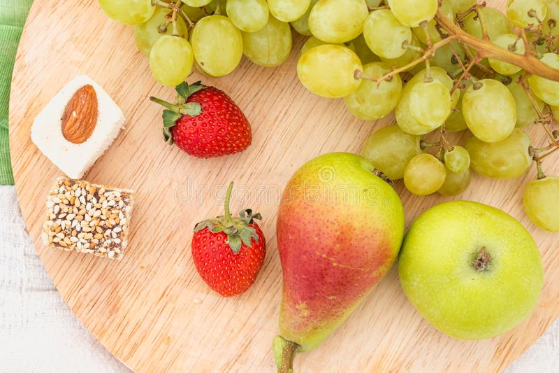 Lato pinkin w łące na zielonej trawie Owocowy kosz, sok i butelkowy wino, arbuz, truskawki w a zdjęcia stock
