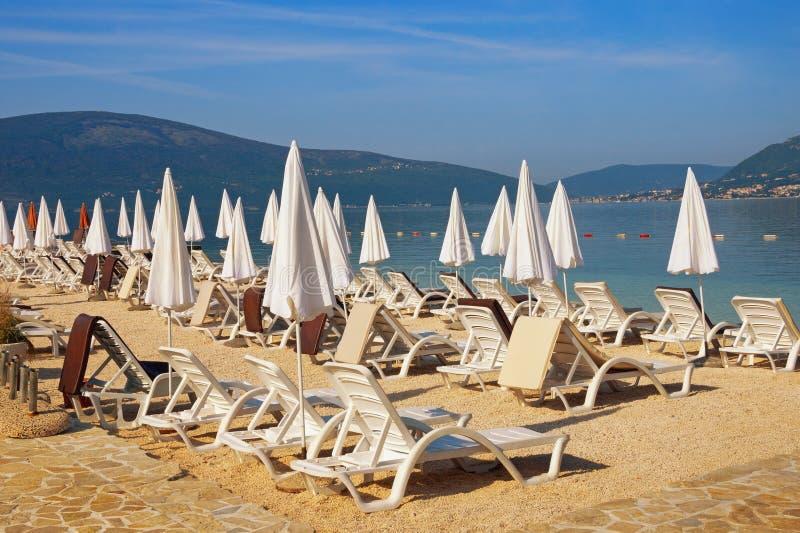 Lato plaży wakacje Pogodny Śródziemnomorski krajobraz z białymi plażowymi parasolami Montenegro, Adriatycki morze, zatoka Kotor zdjęcia royalty free