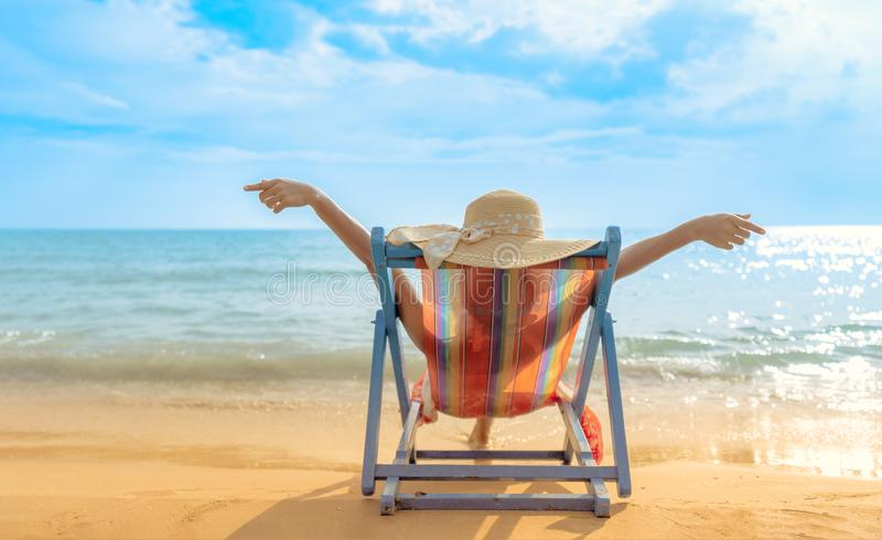 Lato plaży wakacje pojęcie, Azja kobieta z kapeluszowy relaksować i ręka na w górę krzesło plaży przy Koh Mak, Trad, Tajlandia zdjęcie stock