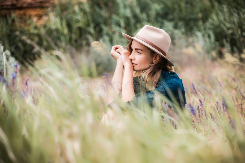 Lato portret młody modniś kobiety obsiadanie w trawie na słonecznym dniu obraz stock
