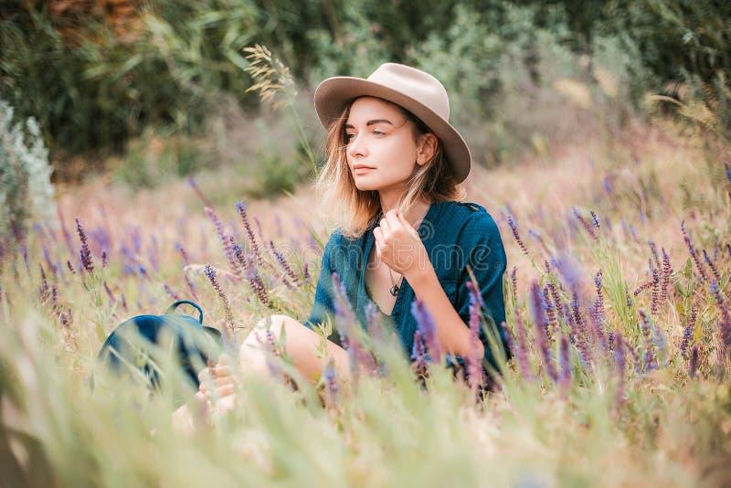 Lato portret młody modniś kobiety obsiadanie w trawie na słonecznym dniu zdjęcie stock