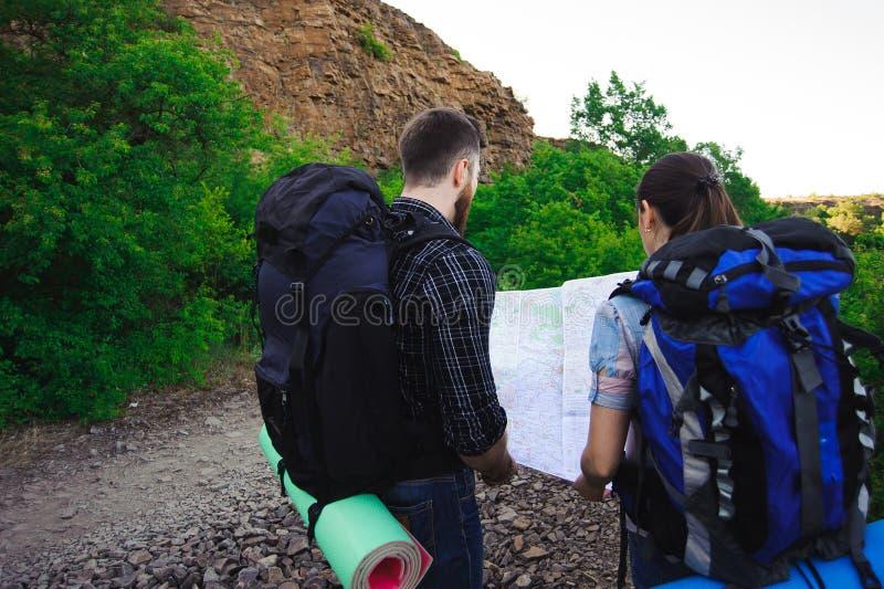 Lato posteriore dei viaggiatori che cercano giusta direzione sulla mappa, sulla libertà e sul concetto attivo di stile di vita fotografie stock