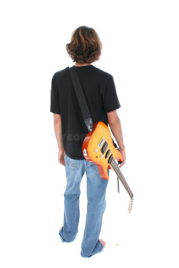 Lato posteriore del ragazzo teenager con la chitarra elettrica sopra bianco fotografia stock