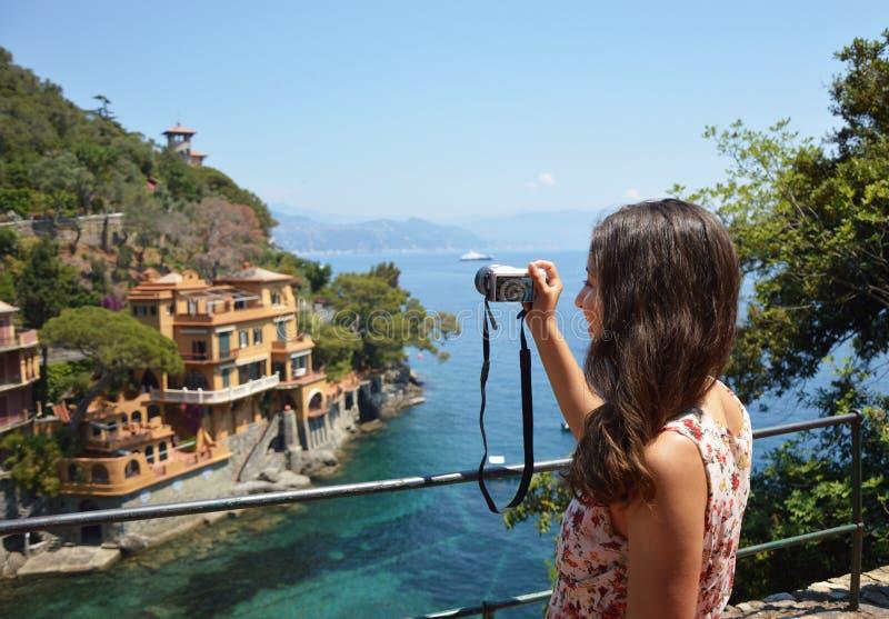 Lato posteriore della giovane donna che prende immagine di bella baia italiana in Portofino, viaggio felice ad Europa, concetto d immagine stock