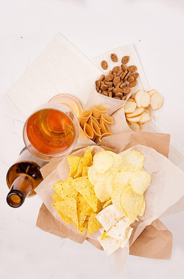 Lato przekąski i lager piwo w szkle - nachos, croutons, układy scaleni, tortilla na rzemiosło papierze na białym drewnianym tle,  zdjęcie royalty free