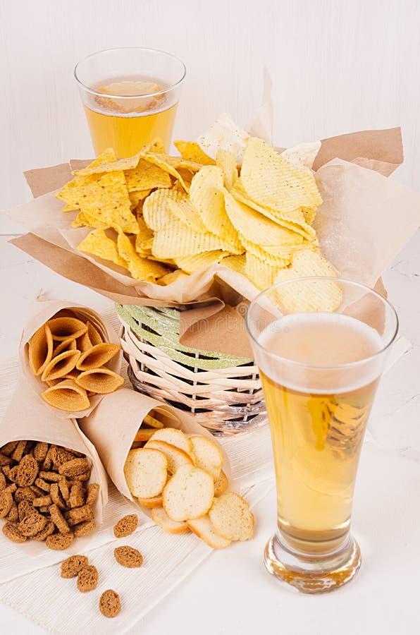 Lato przekąski i lager piwo w szkle - nachos, croutons, układy scaleni, tortilla w nieociosanym koszu i papier, osaczają na białe zdjęcie royalty free