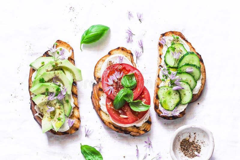 Lato różnicy kanapki - z kremowym serem, avocado, pomidorem i ogórkiem na lekkim tle, odgórny widok Zdrowa dieta fo zdjęcia stock