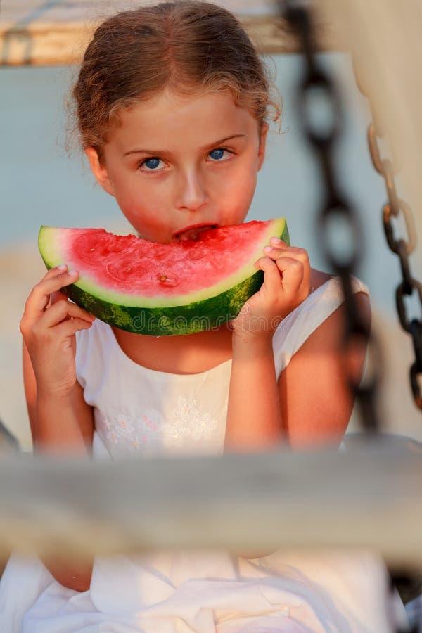 Lato radość, urocza dziewczyna je świeżego arbuza na plaży zdjęcia royalty free