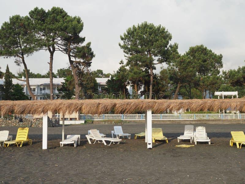 Lato, słońce, dezerterował plażę wybrzeże z słońc loungers Wyrzucać na brzeg morzem z pustymi pokładów krzesłami ustawiającymi z  obraz royalty free