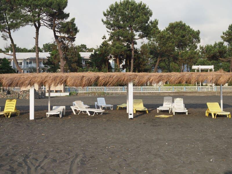 Lato, słońce, dezerterował plażę wybrzeże z słońc loungers Wyrzucać na brzeg morzem z pustymi pokładów krzesłami ustawiającymi z  obrazy stock
