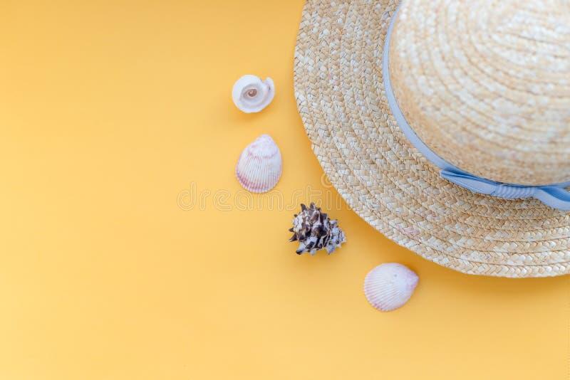 Lato słomianego kapeluszu plaża z seashells na żółtym tle Lat akcesoria Mieszka? nieatutowi pla?owi akcesoria Poj?cie dla fotografia royalty free