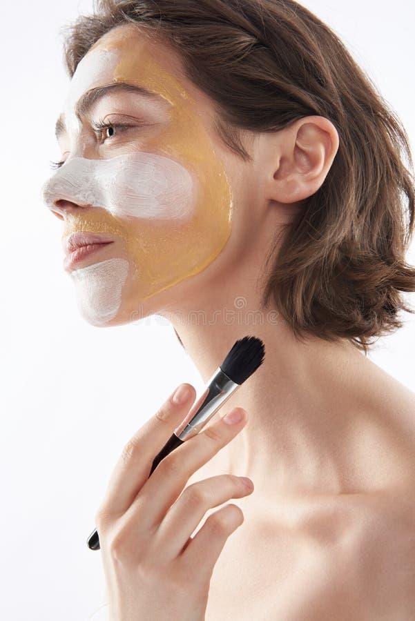 Lato sopra della donna con la maschera e la spazzola di protezione fotografia stock