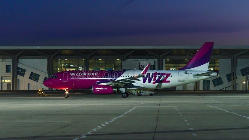 Lato sparato dell'aeroplano del wizzair all'aeroporto al crepuscolo dopo il tramonto immagini stock libere da diritti