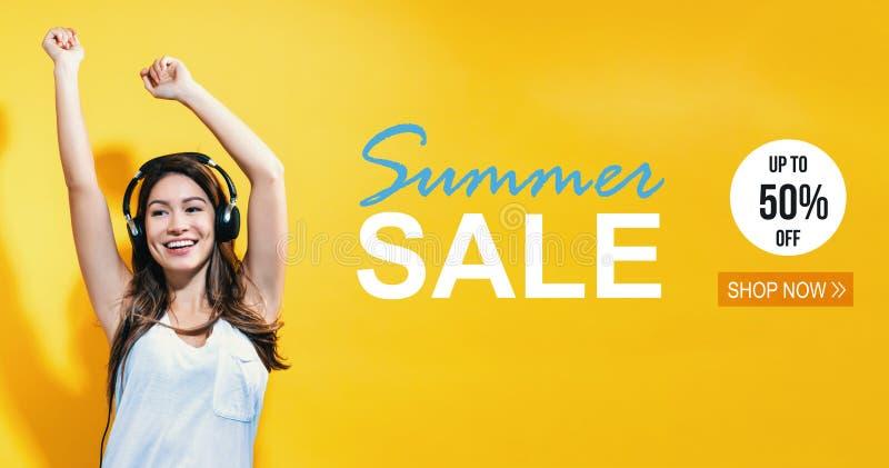 Lato sprzedaż z szczęśliwą młodą kobietą z hełmofonami fotografia royalty free