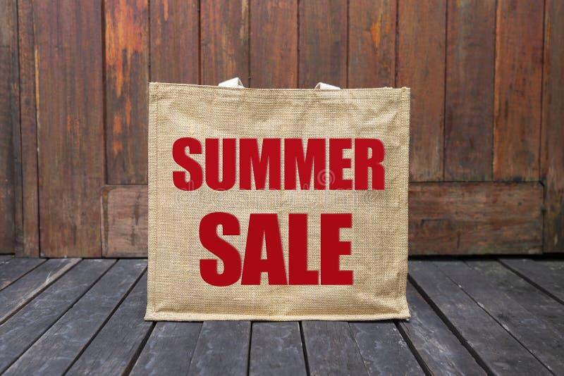 Lato sprzedaży logo na brown jutowej torbie na drewnianej podłoga fotografia stock
