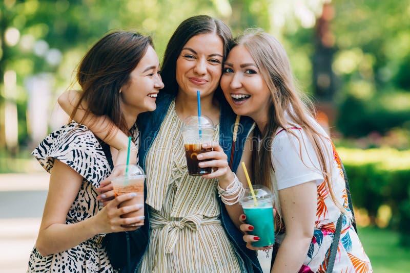 Lato stylu życia portreta multiracial kobiety cieszą się ładnego dzień, trzyma szkła milkshakes Szczęśliwi przyjaciele w parku da obraz royalty free