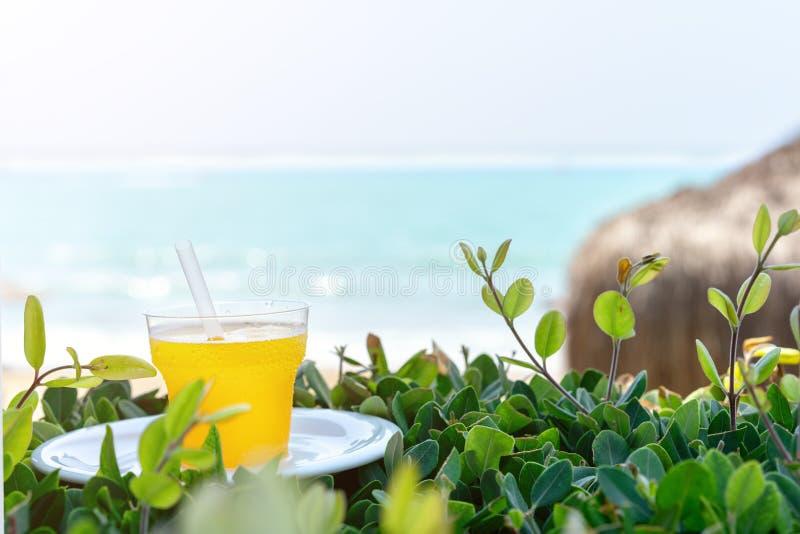 lato, szkło świeży sok od żółtych tropikalnych owoc na plaży na zielonej trawie przeciw tłu morze, obrazy royalty free