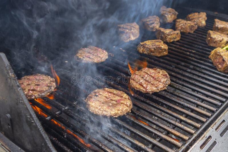 Lato wołowiny hamburger i jagnięcych kotlecików BBQ na propanu gazu grillu płoniemy zdjęcia royalty free