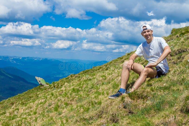 Lato wycieczkuje w górach Młody turystyczny mężczyzna w nakrętce z rękami up na wierzchołku góry podziwia naturę zdjęcie stock