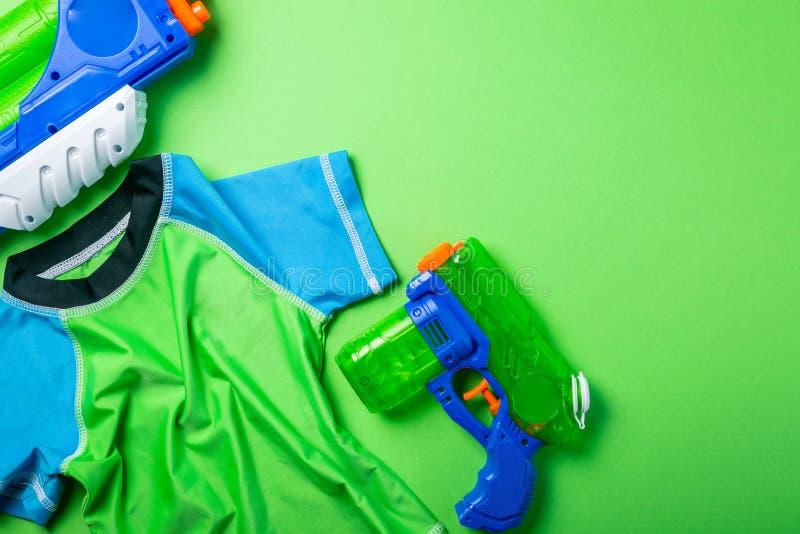 Lato zabawy pojęcie - wodny pistolet i wysypka strażnik na jaskrawym tle zdjęcia stock