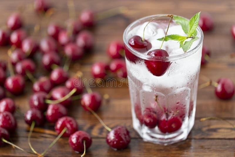 Lato zamrażający napój - wiśnia z lodem Na nieociosanym drewnianym stole obraz stock
