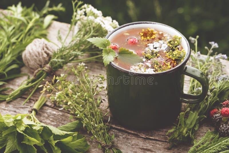 Lato zdrowa ziołowa herbata w starym emaliującym kubku i wiązkach hea zdjęcia stock