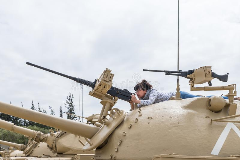 The woman is on the turret of the tank and studies the machine gun on the Memorial Site near the Armored Corps Museum in Latrun, I stock photography