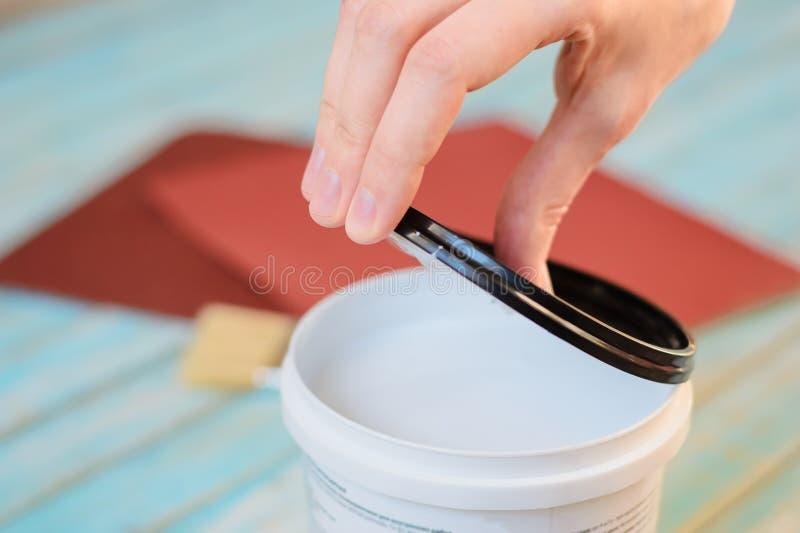 Latta aperta della mano della donna di pittura bianca e bordi di legno che preparano per dipingere fotografia stock