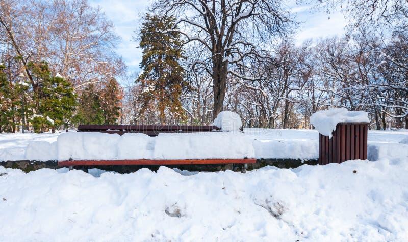 Latta del banco di legno e dell'immondizia o del ciarpame sulla via o nel parco coperto di neve nella stagione invernale nelle om fotografia stock
