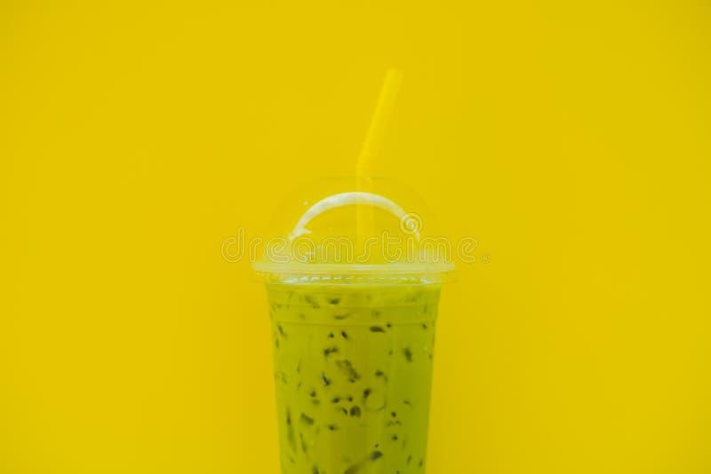 Latte зеленого чая с льдом в пластиковых чашке и соломе в женской руке с желтым маникюром на желтой предпосылке домодельно стоковые изображения rf