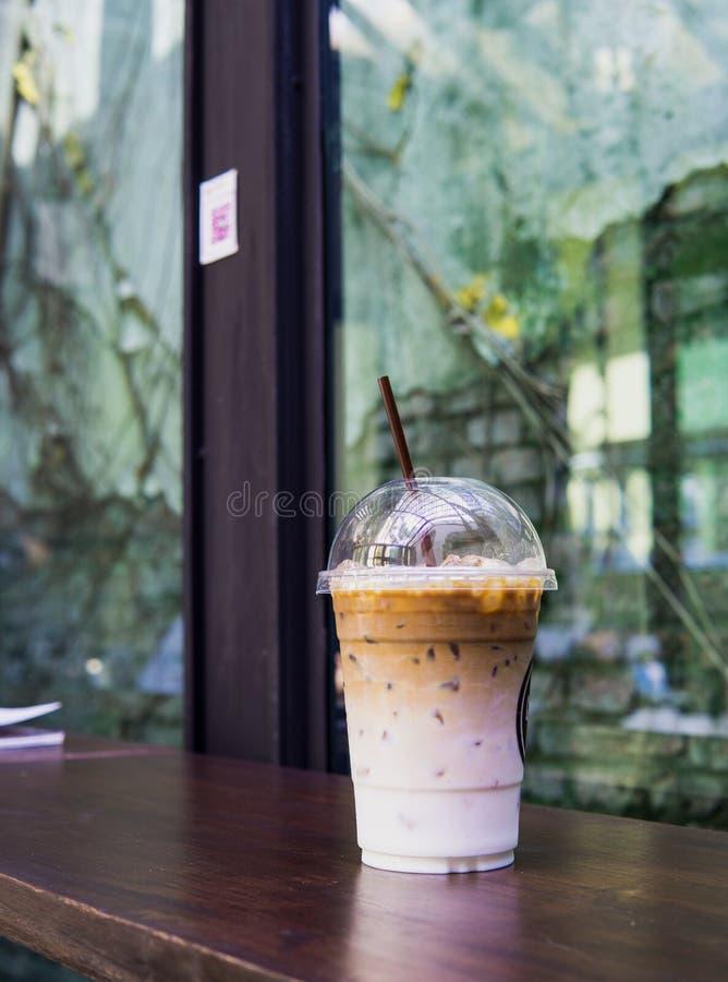 Latte кофе льда в на вынос чашке на деревянной таблице На вынос latte льда в пластичной чашке с соломой на деревянной таблице Пре стоковое фото