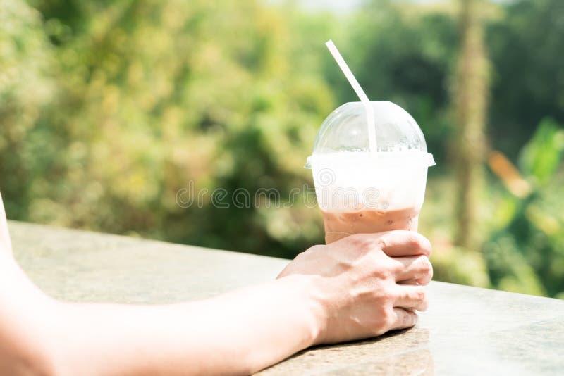 Latte кофе льда на солнечности утра с зелеными предпосылками дерева стоковое фото rf
