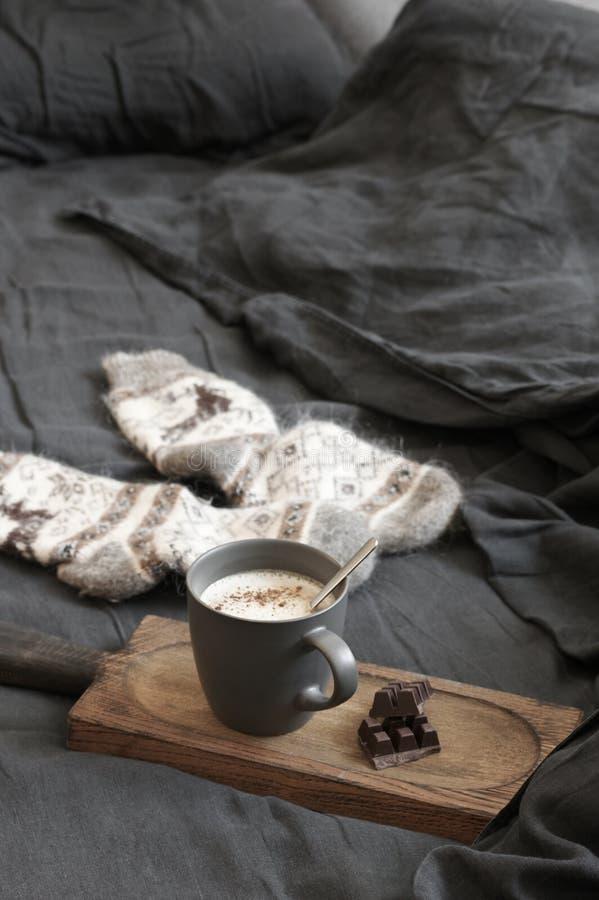 Latte кофе с шоколадом и шерстяные носки в отменятьой кровати стоковое фото