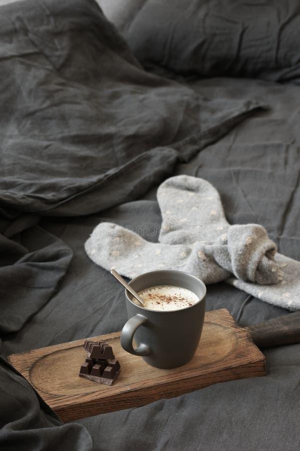 Latte кофе с шоколадом и шерстяные носки в отменятьой кровати стоковые фото