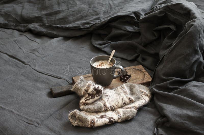 Latte кофе с шоколадом и шерстяные носки в отменятьой кровати стоковые изображения rf
