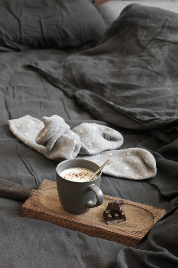 Latte кофе с шоколадом и шерстяные носки в отменятьой кровати стоковые изображения