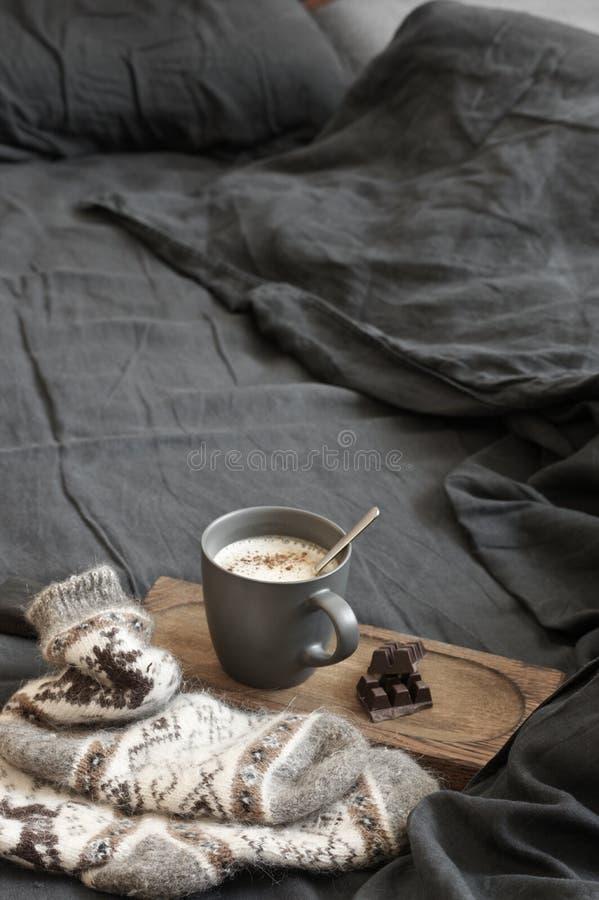 Latte кофе с шоколадом и шерстяные носки в отменятьой кровати стоковая фотография