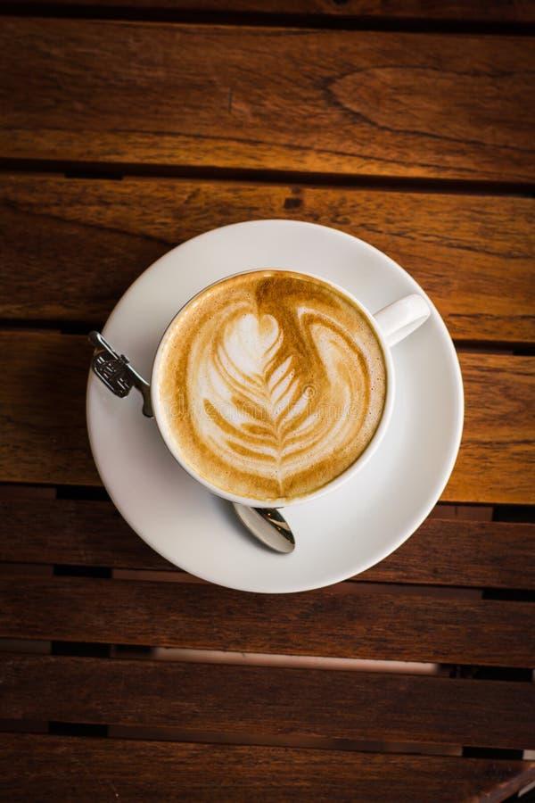 Latte чашки кофе на деревянном столе в утре стоковая фотография