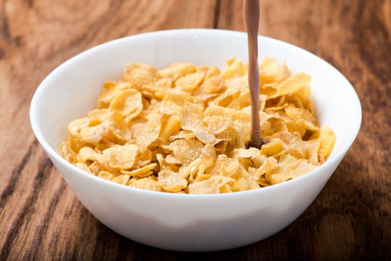 Latte al cioccolato di versamento del cereale dei fiocchi di granturco sulla tavola di legno immagine stock libera da diritti