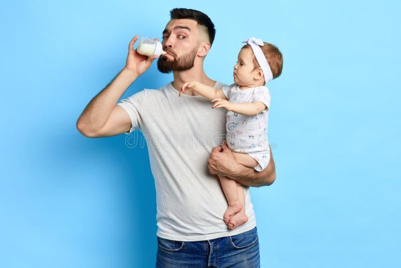 Latte alimentare del giovane padre pazzo dalla bottiglia della sua piccola figlia immagini stock libere da diritti