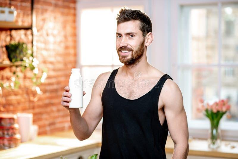 Latte alimentare dell'uomo di sport a casa immagine stock libera da diritti