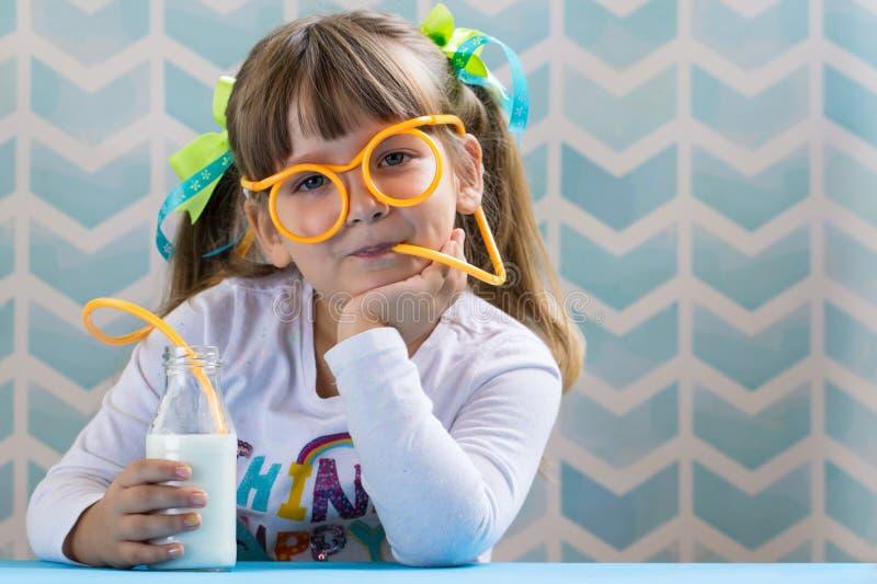 Latte alimentare della bambina dolce con la paglia divertente di vetro immagine stock libera da diritti