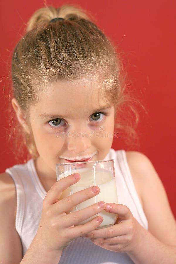 Latte alimentare della ragazza con latte m. immagine stock libera da diritti