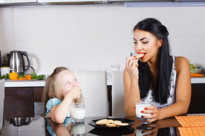 Latte alimentare e biscotti della bella bambina fotografie stock libere da diritti